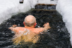 A man in years swims in the ice hole Royalty Free Stock Photography
