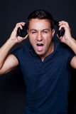 Man yelling while listening to headphones Royalty Free Stock Photos