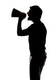 Man yelling in a megaphone. In silhouette isolated over white background Royalty Free Stock Photography