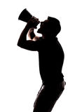 Man yelling in a megaphone. In silhouette isolated over white background Royalty Free Stock Images