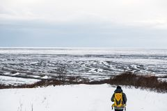 A man with yellow backpack walking on snow mountain in winter, at Iceland Royalty Free Stock Image