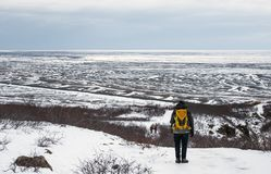 A man with yellow backpack walking on snow mountain in winter, at Iceland Stock Image