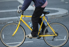 Man on yellow bicycle. A man standing on an old yellow racing style bicycle, on a public road Royalty Free Stock Images