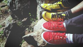 Man in Yellow and Black Low Top Sneakers Beside Red and White Low Top Sneakers Royalty Free Stock Photo