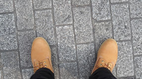 Man yellow boot shoe top view . Man yellow boot shoe top view and stone floor Stock Image