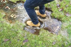 Man in yellow boots plays hopscotch and jumps into squares with numbers flooded with water during a thaw on a playground in the. Countryside, on a spring day royalty free stock photography