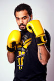 A man with yellow boxing gloves Stock Image