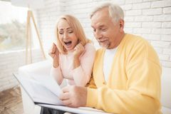 A man in a yellow cardigan and a woman in a pink sweater are sitting and reading documents in a black folder. Royalty Free Stock Photography
