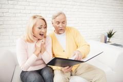 A man in a yellow cardigan and a woman in a pink sweater are sitting and reading documents in a black folder. Stock Photos