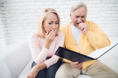 A man in a yellow cardigan and a woman in a pink sweater are sitting and reading documents in a black folder. Royalty Free Stock Photo