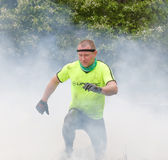 Man in yellow clothes jumping over fire and smoke Royalty Free Stock Image