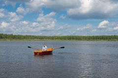 A man in yellow glasses, floating on the lake, on a boat with oars, against a beautiful landscape stock photos