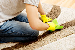 Man in yellow gloves cleaning carpet Stock Photo