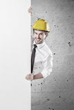 Man with yellow hard hat holding a white banner Stock Photo