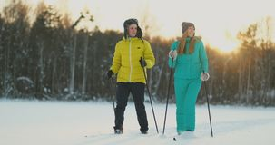 A man in a yellow jacket and a girl in a blue jumpsuit skiing in slow motion at sunset stock footage