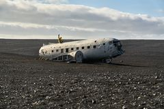 Plane wreckage in Iceland. Man in yellow jacket sits on the abandoned plane wreckage on the Solheimasandur beach on the background of the partially cloudy sky in Royalty Free Stock Photography