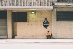 Man in Yellow Jacket Sitting on White Waiting Shed Stock Images