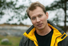 Man in yellow jacket smiles Royalty Free Stock Photography