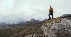 A man in a yellow jacket stands on a stone against a background of snow-covered mountain peaks in a fog.  stock footage