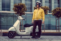 A man in yellow jacket and sunglasses posing near white scooter. Man in yellow jacket and sunglasses posing near white scooter Royalty Free Stock Photography