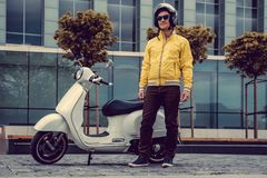 A man in yellow jacket and sunglasses posing near white scooter. Man in yellow jacket and sunglasses posing near white scooter Royalty Free Stock Photo