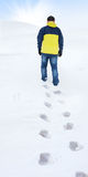 Man in yellow jacket walking on snow Royalty Free Stock Photos