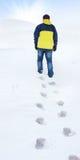 Man in yellow jacket walking on snow Royalty Free Stock Photos