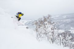 Man in yellow jumps off a cornice near the summit of a small peak in the backcountry of Hokkaido, Japan. Backcountry skier jumps off a cornice near the summit of stock photos
