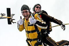 Man in Yellow Jumpsuit and Man in Black Jumpsuit Sky Diving Royalty Free Stock Photography
