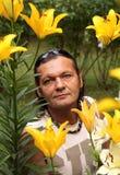 The man among yellow lilies. Summer, greens, flowers, garden and the man among lilies Stock Images