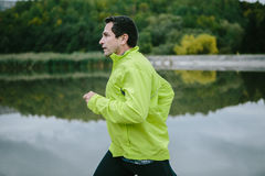 Man in yellow neon jacket runnig at the lake Stock Photos
