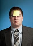 Man With Yellow Note. Businessman with yellow sticky note on forehead Stock Images