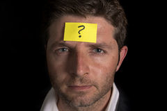 Man with yellow postit note on his forehead. Business man with a yellow posit note on his face with a question mark written on it Stock Images