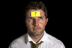 Man with yellow postit note on his forehead Royalty Free Stock Image