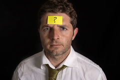Man with yellow postit note on his forehead. Business man with a yellow posit note on his face with a question mark written on it Stock Image