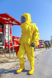 Man in yellow protective hazmat suit and fire trucks. Blue sky Royalty Free Stock Photos
