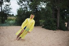 Man in yellow raincoat blown away by the wind falls. He falls Royalty Free Stock Image