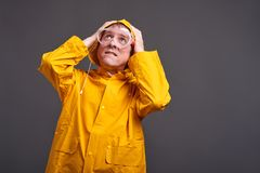 Man in yellow raincoat. A middle aged man in a yellow raincoat and safety glasses feeling scaredr royalty free stock image