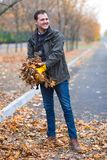 A man in yellow rubber gloves removes the autumn fallen leaves, in the park. stock photo