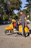 Man with yellow scooter Royalty Free Stock Photography