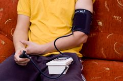 Man in yellow shirt is checking blood pressure stock photos