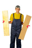 Man in the yellow shirt in overalls holding two boards Royalty Free Stock Image