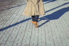 A man in yellow shoes walking along the pavement. On day Royalty Free Stock Images