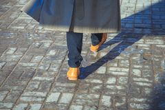 A man in yellow shoes walking along the pavement. On day Stock Photos