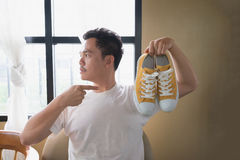 A man and yellow sneakers. A man is sitting and holding yellow sneakers and pointing to shoes as they are the love of his life Royalty Free Stock Photo