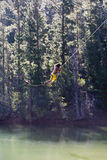 Man, in yellow swimming shorts, swinging on rope above lake, side view Royalty Free Stock Photography