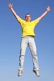 Man in yellow t-shirt. Jump. Boy in yellow t-shitt on blue background Royalty Free Stock Photos