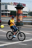 A man in yellow t-shirt rides a bycicle Stock Images