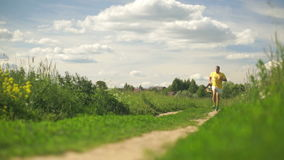 Man in a yellow t-shirt running across the summer field. Clip stock footage