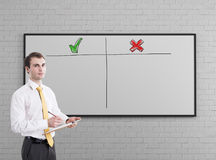 Man in a yellow tie, pros and cons. Portrait of a young businessman with a clipboard wearing a white shirt and a tie and standing near a whiteboard with a pros Royalty Free Stock Image
